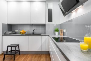 Light and spacious high-gloss kitchen in white with wooden floor panels